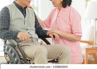 Home helper carer and senior man in wheelchair