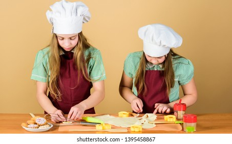 The home of high class baking. Small children taking cooking class together. Little girls preparing cookies in cooking class. Master class in pastry baking.