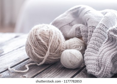 home hobbies, cozy knitted sweaters with a ball of yarn in the living room on a wooden background
