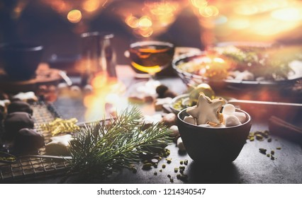 Home holidays cuisine and sweet gifts making for Christmas. Mug with marshmallows and cinnamon star Christmas cookie on table with nuts , chocolate and fir brunches. Cozy festive homely atmosphere