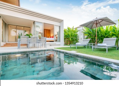 home or house Exterior design showing tropical pool villa with greenery garden, sun bed, umbrella, pool towels