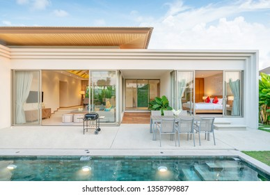 home or house Exterior design showing tropical pool villa with greenery garden, sun bed, umbrella, pool towels ,dining table