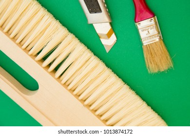 Home, House Repair, Redecorating, Renovating Concept. A wooden brush, a paint brush and a paper knife on a green background, top view, flat lay