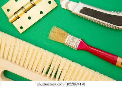 Home, House Repair, Redecorating, Renovating Concept. A wooden brush, a door hinge,a paint brush and a paper knife on a green background, top view, flat lay