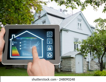 home, housing, people and technology concept - close up of man hands pointing finger to tablet pc computer and regulating room temperature over house background