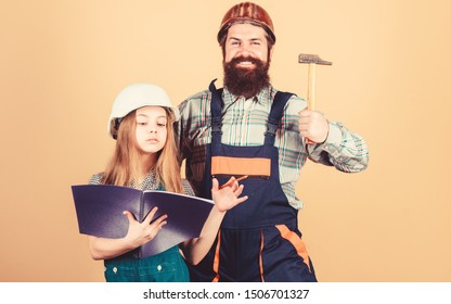 Home improvement activity. Kid girl planning renovation. Child renovation room. Family remodeling house. Little fathers helper. Father bearded man and daughter hard hat helmet uniform renovating home.