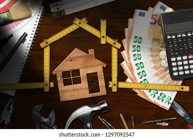 Home improvement concept - Wooden folding ruler in the shape of a house with work tools, calculator, banknotes and coins on a wooden desk