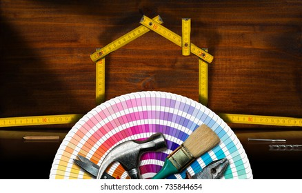 Home improvement concept - Wooden folding ruler in the shape of a model house with work tools on a desk