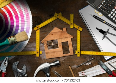 Home improvement concept - Wooden model house with folding ruler, work tools and a calculator on a wooden desk