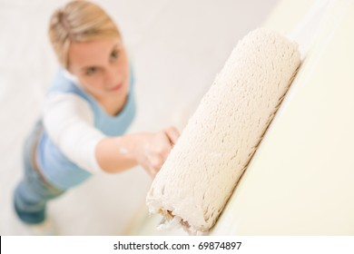 Home improvement - handywoman painting wall with roller
