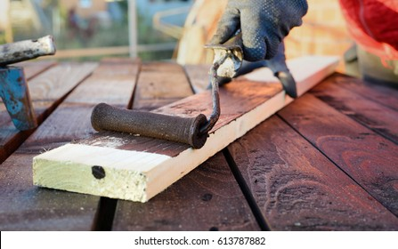 Home improvement - handywoman painting wooden plank outdoors