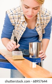 Home improvement - handywoman painting wooden plank in workshop