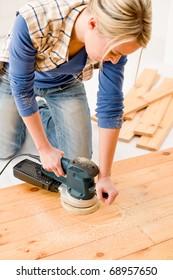 Home improvement - handywoman sanding wooden floor in workshop