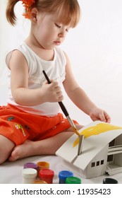 Home Improvement - Little Girl repairs. Child colors by paint the mock-up of the house
