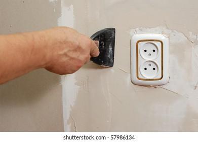 home improvement - man stop up wall near socket