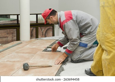 Home improvement, renovation - construction worker tiler is tiling, ceramic tile floor adhesive, trowel with mortar