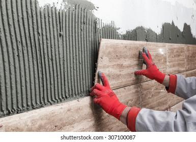 Home improvement, renovation - construction worker tiler is tiling, ceramic tile wall adhesive