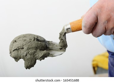 Home improvement, renovation - Hand holding a bucket trowel with cement mortar in construction site
