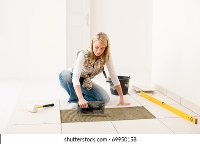 Home improvement, renovation - handy woman laying tile, trowel with mortar