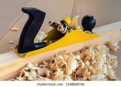 Home improvement.Pine shavings and hand plane. Treatment of a wooden block with a yellow plane and curled shavings on a workbench. Horizontal shot.