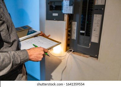 home Inspector in front of electric distribution board during inspection, selective focus and close up on man's hands as he holding notebook and pen