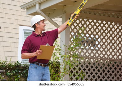 A home inspector or house building repair contractor in a hard hat holding a level and a clipboard outside a home doing an inspection or construction quote
