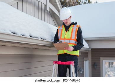 Home inspector on a ladder while writing on a clipboard during winter.