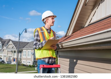 Home inspector standing on a ladder and providing an inspection to the roof of a house.