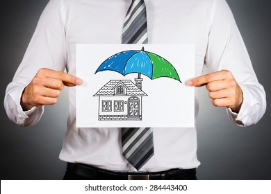 Home insurance concept. Businessman holding paper with drawing of a house under the umbrella.