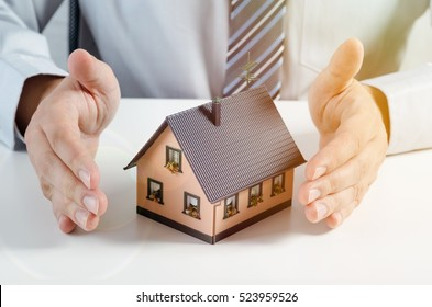 Home insurance concept. Businessman with house miniature