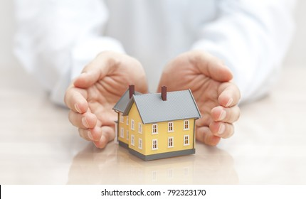 Home insurance concept. Small yellow house covered by hands.