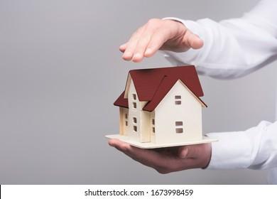 Home insurance concept.Businessman holding home model.