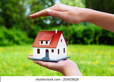 Home insurance concept.Photo of a hand hovering over a miniature house