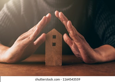 home insurance ideas concept with man hand protect house wooden model from risk and problem