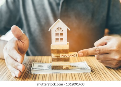 Home insurance or Property protection concept. Insurance agent complete wooden model of the house with text insurance.