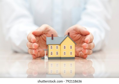 Home insurance. Small yellow house covered by hands.