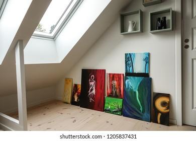 Home interior. Art collection in modern attic / loft apartment. Skylight window.
