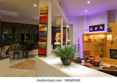 Home interior with artwork, grand piano, and accent illumination.