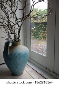 Home interior beautiful designer curly natural willow wood branches in copper blue gold earthenware amphora pot with large handle by light of glass door set on ancient oak wood plank flooring indoors