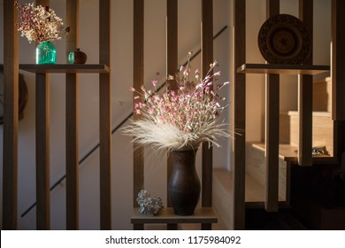 Home interior decor with clay brown jar with dried purple and white flowers . Living room decoration. rior. of style, design an dint
