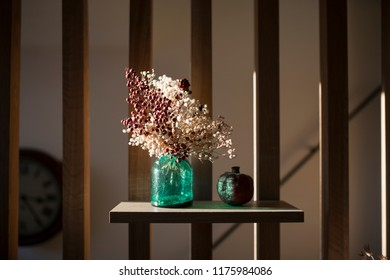 Home interior decor with clay green glass vase jar with dried purple and white flowers . Living room decoration. rior. of style, design an dint
