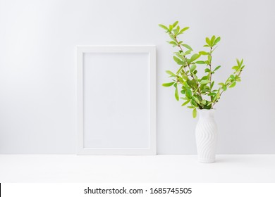 Home interior with decor elements. Mockup with a white frame and branches with green leaves in a vase on a light background