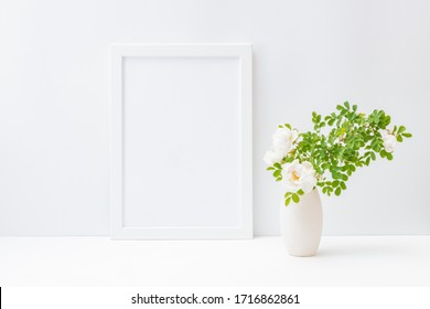 Home interior with decor elements. Mockup with a white frame and small flowers and green leaves in a vase on a light background