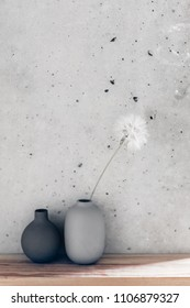 Home interior decor in scandinavian minimalistic style: ceramic vases on the wooden shelf over concrete wall. Living room decoration in gray colors.