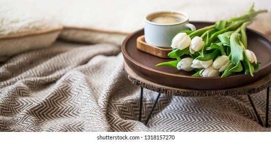 Home interior decor with wooden table, tulips flower bouquet and coffee cup, cozy blanket, spring interior lifestyle decorations