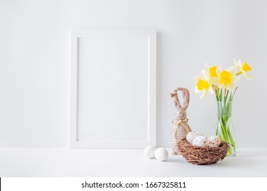 Home interior with easter decor. Mockup with a white frame and yellow daffodils in a glass vase on a light background