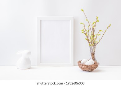 Home interior with easter decor. Mockup with a white frame and willow branches in a vase on a light background