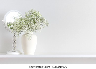 Home interior floral decor. Beautiful flowers in a vase on a white wall background. White flowers, mirror on a wooden shelf.