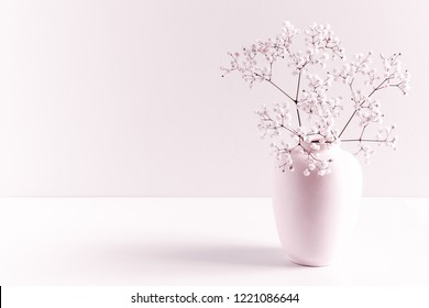 Home interior floral decor. Elegant floral soft pink composition. Beautiful flowers in  vase on pastel pink wall background.