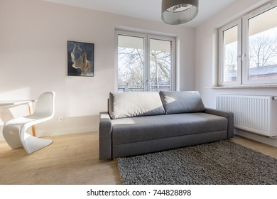 Home interior with gray couch and modern chair